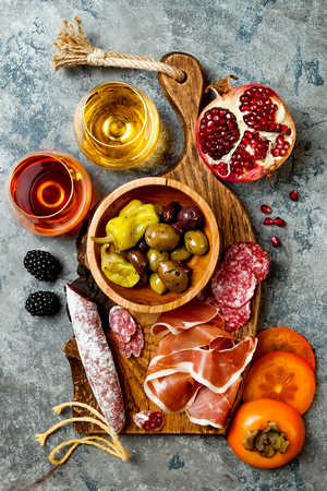 Appetizers table with italian antipasti snacks and wine in glasses. Charcuterie board over grey concrete background. Top view, flat lay Reklamní fotografie