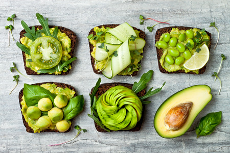 Fresh avocado toasts with different toppings. Healthy vegetarian breakfast with rye wholegrain sandwiches