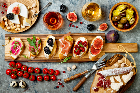 Appetizers table with italian antipasti snacks and wine in glasses. Brushetta or authentic traditional spanish tapas set, cheese variety board over grey concrete background. Top view, flat lay Foto de archivo