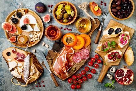 전채 테이블 이탈리아어 antipasti 스낵 및 안경 와인. Brushetta 또는 본격적인 전통 스페인어 타파스 설정, 회색 콘크리트 배경 위에 치즈 다양 한 보드. 평