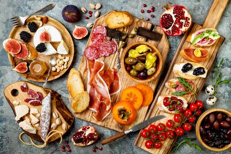 Tabela dos aperitivos com os petiscos italianos dos antipasti. Brushetta ou tapas espanhóis tradicionais autênticos ajustam-se, placa da variedade do queijo sobre o fundo concreto cinzento. Vista superior, lay plana