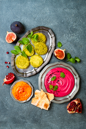 Middle Eastern traditional food. Authentic arab cuisine. Vegan green baked falafel, roasted beet and pumpkin hummus. Top view, flat lay, overhead  Stock Photo