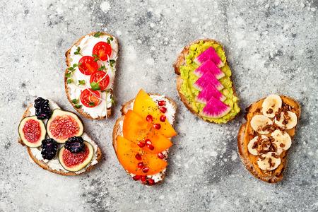 Healthy breakfast toasts with peanut butter, banana, chocolate granola, avocado, watermelon radish, persimmon, pomegranate, chia seeds, tomato, figs, blackberry.  Stock Photo