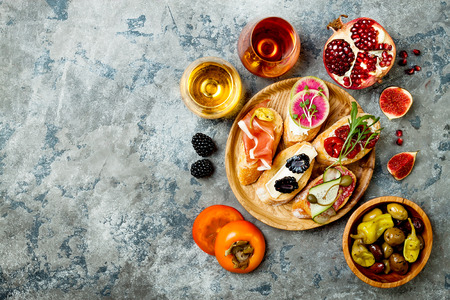 Appetizers table with italian antipasti snacks and wine in glasses. Brushetta or authentic traditional spanish tapas set, cheese variety board over grey concrete background. Top view, flat lay, copy space