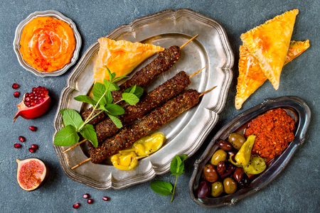 Middle Eastern traditional dinner. Authentic arab cuisine. Lamb kebab, sambusek, muhammara, pumpkin hummus. Top view, flat lay, overhead  Stock Photo