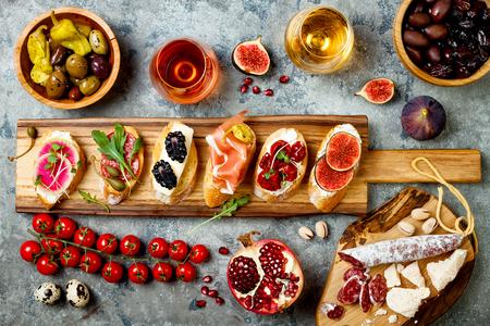 Apéritif table avec des snacks italiens antipasti et du vin dans des verres. Brushetta ou authentique ensemble de tapas espagnoles traditionnelles, plateau de variétés de fromage sur fond de béton gris. Vue de dessus, pose plate