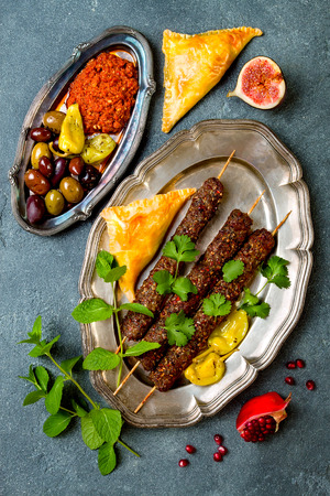Middle Eastern traditional dinner. Authentic arab cuisine. Meze party food. Lamb kebab, sambusek, muhammara.Top view, flat lay, overhead
