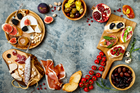 Appetizers table with italian antipasti snacks. Brushetta or authentic traditional spanish tapas set, cheese variety board over grey concrete background. Top view, flat lay, copy space Stock Photo - 90380769