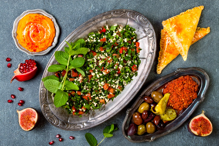 Middle Eastern traditional dinner. Authentic arab cuisine. Tabbouleh, sambusek, muhammara, pumpkin hummus. Top view, flat lay, overhead  Stock Photo