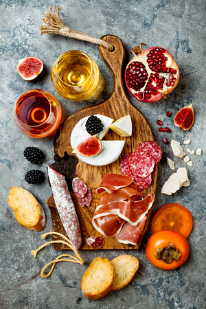Appetizers table with italian antipasti snacks and wine in glasses. Charcuterie and cheese board over grey concrete background. Top view, flat lay