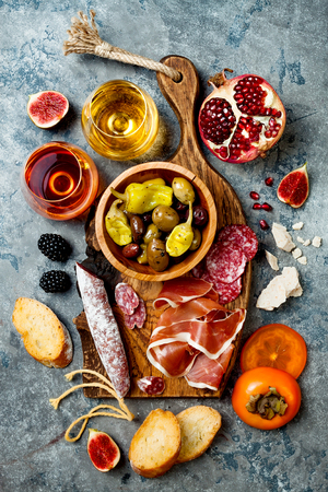 Appetizers table with italian antipasti snacks and wine in glasses. Charcuterie board over grey concrete background. Top view, flat lay Stock Photo