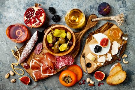 Mesa de aperitivos con aperitivos antipasti italianos y vino en copas. Brushetta o auténtico conjunto de tapas españolas tradicionales, tabla de variedad de queso sobre fondo gris hormigón. Vista superior, endecha plana
