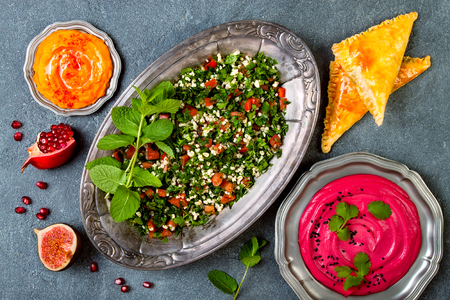 Middle Eastern traditional dinner. Authentic arab cuisine. Tabbouleh, sambusek, pumpkin and beet hummus. Top view, flat lay, overhead
