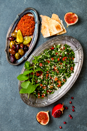Middle Eastern traditional dinner. Authentic arab cuisine. Meze party food. Tabbouleh, muhammara, olives. Top view, flat lay, overhead