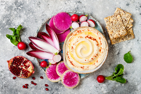 Homemade hummus seasoned with olive oil and paprika and fresh vegetables: radishes, watermelon radish, red chicory, pomegranate. Healthy vegetarian appetizer or snack platter Standard-Bild - 91611646