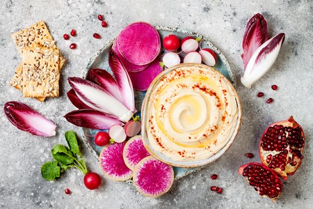 Homemade hummus seasoned with olive oil and paprika and fresh vegetables: radishes, watermelon radish, red chicory, pomegranate. Healthy vegetarian appetizer or snack platter Stock Photo