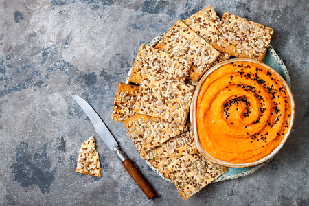 Pumpkin hummus seasoned with olive oil and black sesame seeds with whole grain crackers. Healthy vegetarian appetizer or snack  Stock Photo
