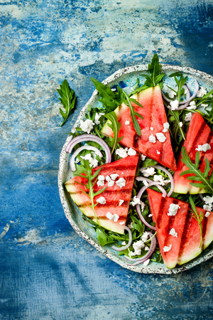Fresh summer grilled watermelon salad with feta cheese, arugula, onions on blue background Фото со стока