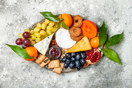 Appetizers table with antipasti snacks. Cheese variety board over grey concrete background. Top view, flat lay