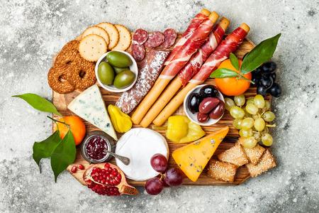 Aperitivos de la mesa con aperitivos antipasti. Tablero de la variedad del queso y de la carne sobre fondo concreto gris. Vista superior, plano