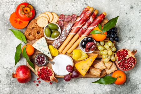 Appetizers table with antipasti snacks. Cheese and meat variety board over grey concrete background. Top view, flat lay