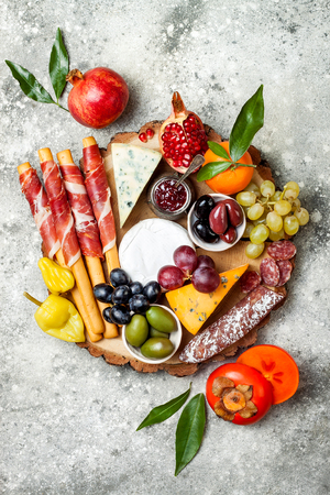 antipasti 간식 전채 테이블입니다. 회색 콘크리트 배경 위에 치즈와 고기 다양 한 보드입니다. 평면도, 평면도, 복사 공간