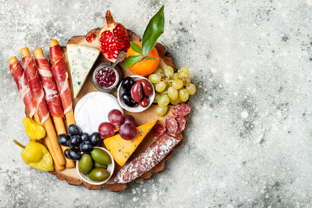Appetizers table with antipasti snacks. Cheese and meat variety board over grey concrete background. Top view, flat lay, copy space Archivio Fotografico