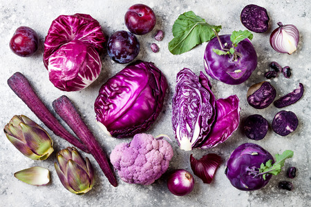 Raw purple vegetables over gray concrete background. Cabbage, radicchio salad, kohlrabi, carrot, cauliflower, onions, artichoke, beans, potato, plums. Top view, flat lay.  Stock Photo