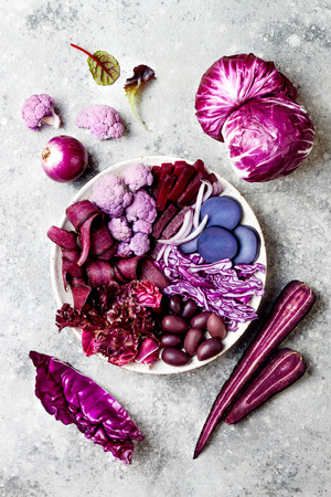 Purple Buddha bowl with spiral carrots, cauliflower, beet, onion, potato, shredded red cabbage, radicchio salad, kalamata olives. Vegan detox veggie bowl