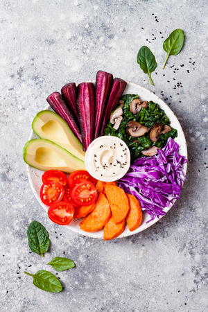 Buddha bowl with roasted butternut, hummus, shredded red cabbage, tomatoes, avocado, purple carrots, sauteed spinach, mushrooms. Healthy vegetarian appetizer or snack platter. Winter veggies detox lunch bowl Stock Photo