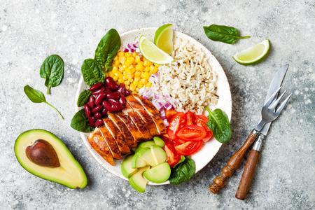Bacia mexicana caseiro do burrito da galinha com arroz, feijões, milho, tomate, abacate, espinafre. Tigela de almoço de salada de taco