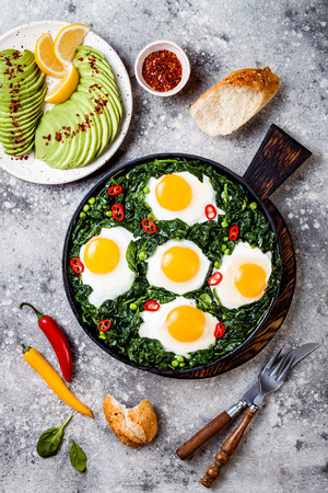 Green shakshuka with spinach, kale and peas. Healthy delicious breakfast with eggs, avocado. Top view, overhead, flat lay