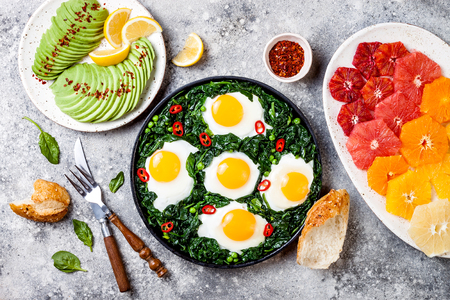 Green shakshuka with spinach, kale and peas. Healthy delicious breakfast with eggs, citrus salad, avocado. Top view, overhead, flat lay Stock Photo