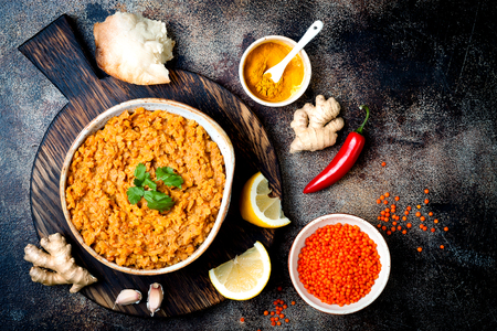 Traditional red lentil Dal. Indian Dhal spicy curry in bowl with flat bread and spices. Top view, overhead