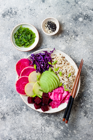Vegan poke bowl with avocado, beet, pickled cabbage, radishes. Top view, overhead, flat lay Stock Photo