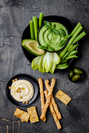 Green vegetables snack board with various dips. Hummus, herb hummus or pesto with crackers, grissini bread, fresh vegetables. Healthy raw summer platter.