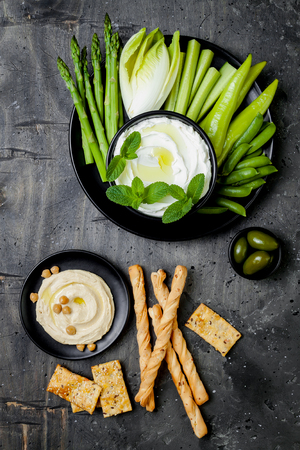 Green vegetables snack board with various dips. Yogurt sauce or labneh, hummus with crackers, grissini bread, fresh vegetables. Healthy raw summer platter.