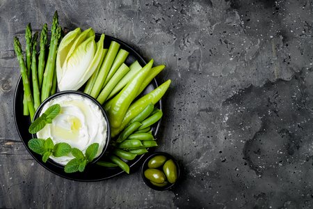 Green vegetables snack board with yogurt sauce or labneh dip. Healthy raw summer platter. Copy space Stockfoto