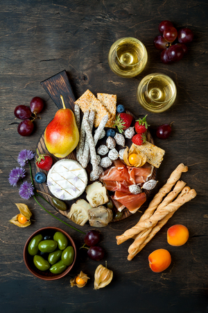 Appetizers table with italian antipasti snacks and wine in glasses. Cheese and charcuterie variety board over rustic wooden background Stock Photo