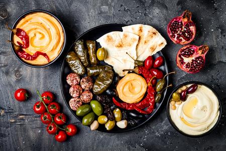 阿拉伯传统美食。中东餐盘,有皮塔饼,橄榄,鹰嘴豆泥,填充的dolma,香料奶酪球。地中海开胃菜派对想法