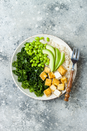 Cauliflower rice Buddha bowl with massaged kale, tofu, avocado and edamame beans. Vegan poke bowl Archivio Fotografico - 103615121