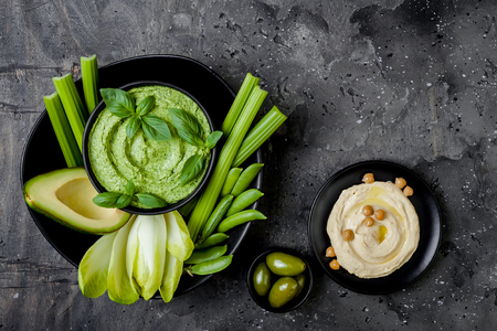 Green vegetables snack board with herb hummus or pesto dip. Healthy raw summer appetizer platter. Copy space Stock Photo - 103615122