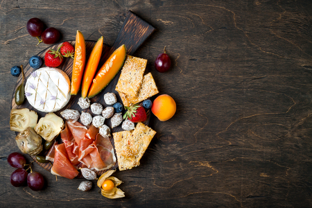 Appetizers table with italian antipasti snacks and wine in glasses. Cheese and charcuterie variety board over rustic wooden background Фото со стока