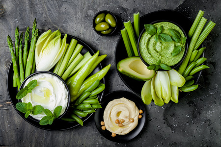 Green vegetables snack board with various dips. Yogurt sauce or labneh, hummus, herb hummus or pesto with fresh vegetables. Healthy raw summer platter. Stockfoto