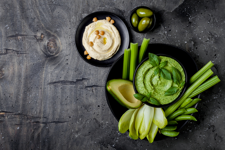 Green vegetables snack board with herb hummus or pesto dip. Healthy raw summer appetizer platter. Copy space