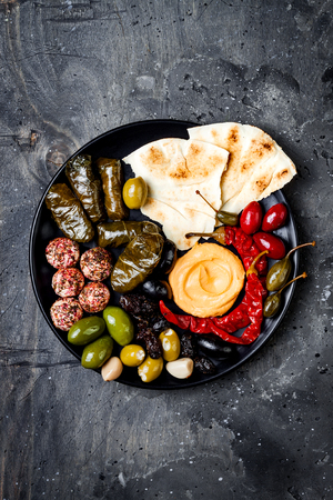 Middle Eastern meze platter with pita, olives, hummus, stuffed dolma, labneh cheese balls in spices. Mediterranean appetizer party idea