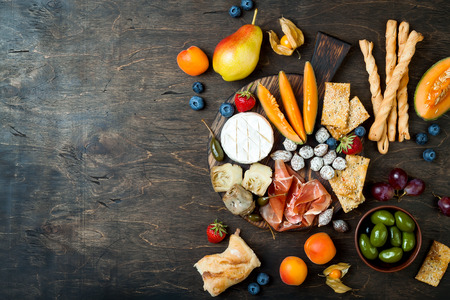 Appetizers table with italian antipasti snacks. Cheese and charcuterie variety board over rustic wooden background