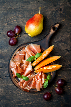 Jamon serrano or prosciutto with melon and fruits over rustic wooden background. Italian or spanish antipasti, appetizer board