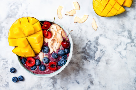 Acai breakfast superfoods smoothie bowl with mango, blueberry, cherry, coconut flakes. Overhead, top view, flat lay. Stock Photo
