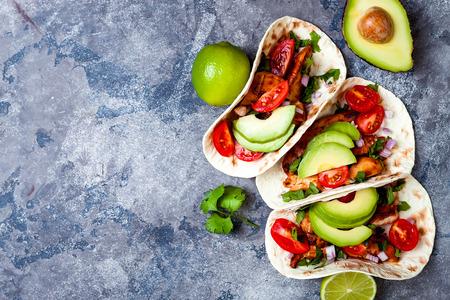 墨西哥烤鸡玉米饼配鳄梨、番茄、洋葱放在质朴的石头桌上。五月节派对食谱。俯视图,头顶,平躺。